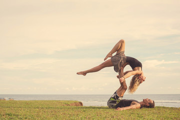 Love beautiful couple on the beach doing fitness yoga exercise together