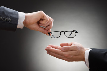 Businessman Giving Eye Glasses To His Colleague