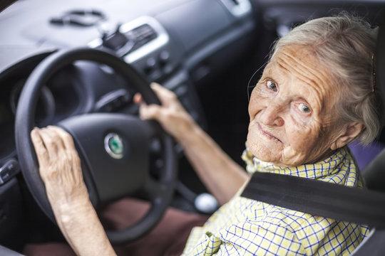 Cheerful senior woman driving a car