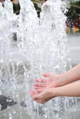 噴水の水を受け止める手.