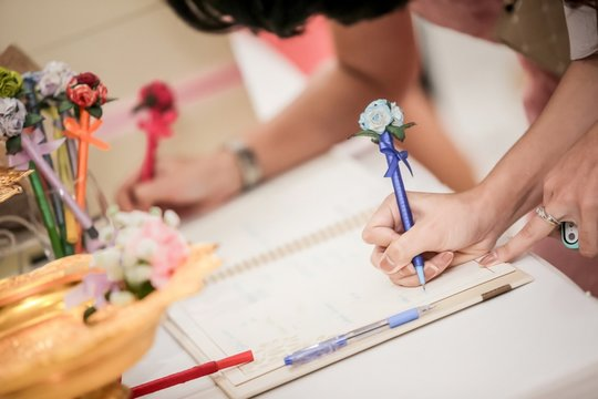 Hand of guests holding pens writing  on a Wedding Signing books