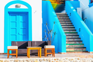 Sofa in front of Greek house painted with blue