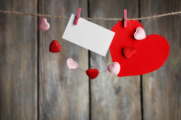 Bright hearts and card hanging on rope on wooden background