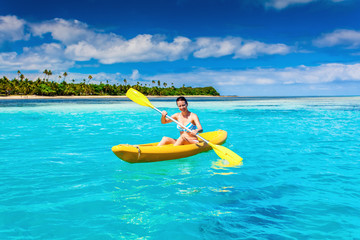 Woman Kayaking in the Ocean on Vacation in tropical island