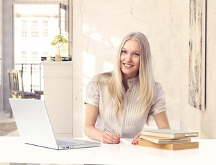 Attractive blonde woman studying at vintage home
