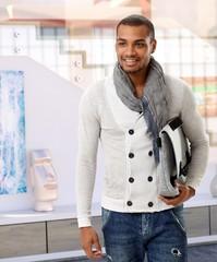 Happy casual arabian man with handbag at gallery