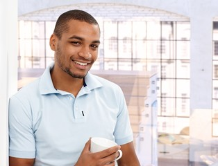 Happy afro american man at loft apartment home