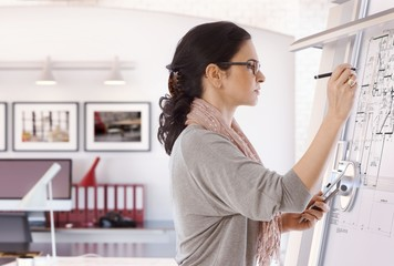 Focused female architect working on drawing board