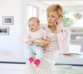 Busy housewife in kitchen with baby and phone