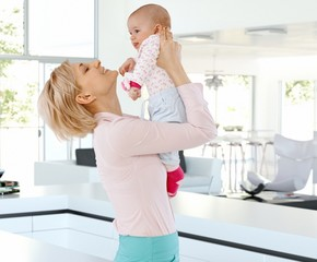 Happy mother with baby at bright home indoors