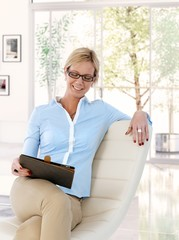 Happy mid adult businesswoman at home with tablet