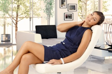 Attractive woman resting in chair at trendy home