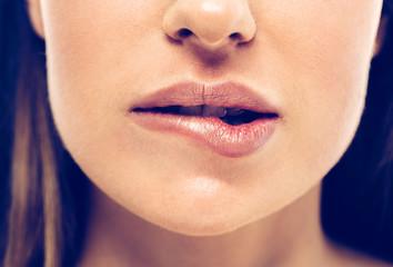 Woman bite lips close up face beautiful