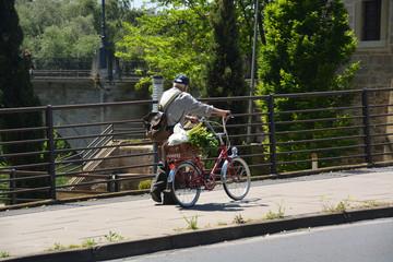hombre mayor empujando una bicicleta