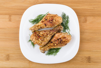 Three fried chicken legs sprinkled pepper with dill in plate