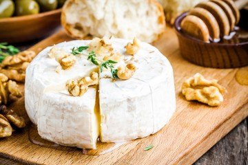 Camembert cheese with walnuts,  honey and thyme closeup