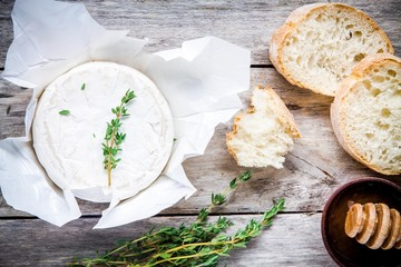 Whole Camembert cheese with thyme, honey and baguette