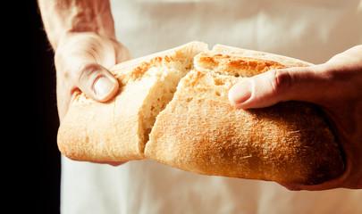 Man breaking a loaf of crusty white bread