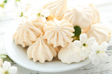 French meringue cookies on plate on white wooden background