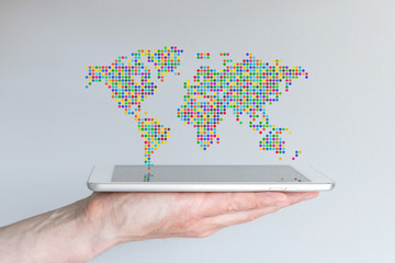 World map floating above a modern smart phone or tablet