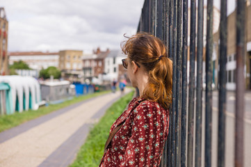 Young woman resting by fence outside