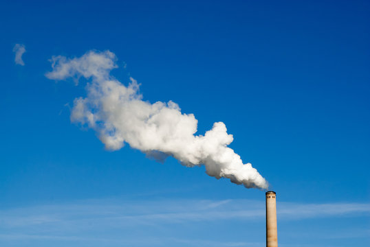 Smokestack and horizontal white smoke on blue sky.