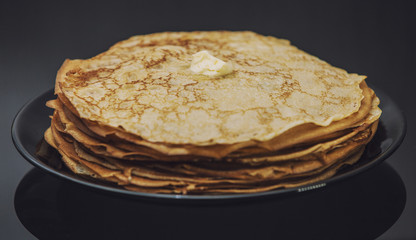 The lot of pancakes on black plate