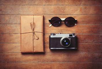 Vintage camera and sunglasses with package on wooden table.