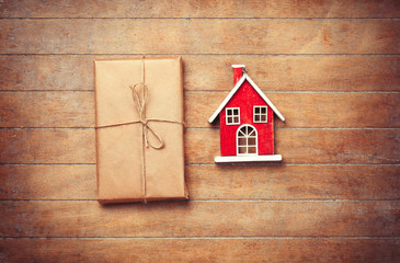 Toy house and package on wooden background.