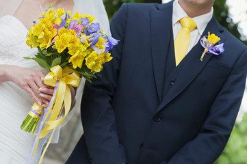 Bride and groom body parts with bouquet