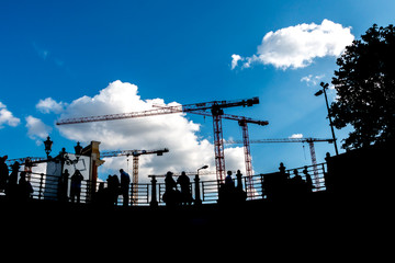 silhouette of people, cranes and clouds