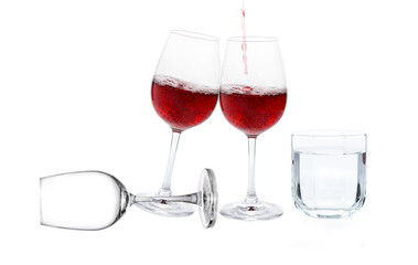 Poured red wine with drinking water on white background
