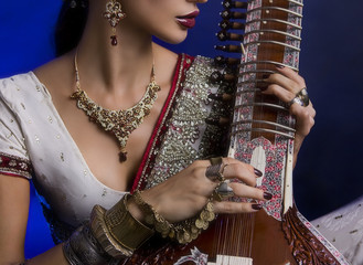 Beautiful Indian Woman in Sari with Oriental Jewelry Playing the