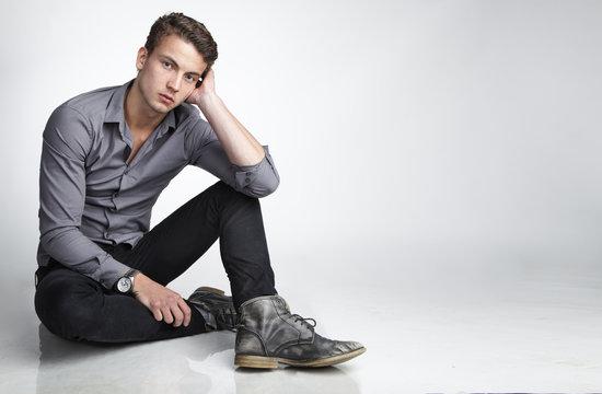 Attraktiver Teenager sitzt auf dem Boden und stützt seinen Kopf ab