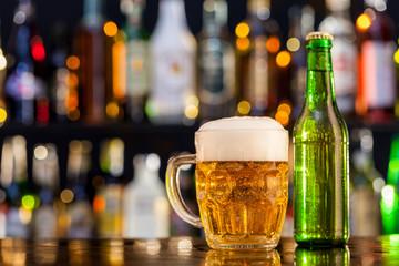 Jug of beer with bottle served on bar counter