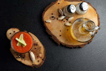 Gazpacho soup and bottle of olive oil on the dark table. Top view
