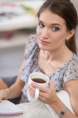 Young beautiful woman with a cup on sofa at home