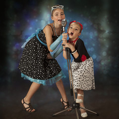 Rockabilly girls posing with vintage microphone