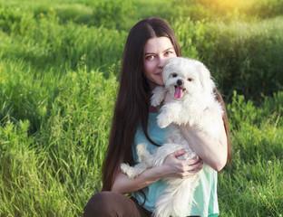 Beautiful brunette with a young dog enjoying a beautiful day