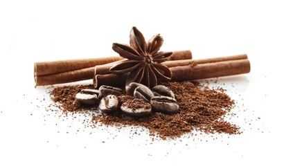 Collected coffee beans with coffee powder on white