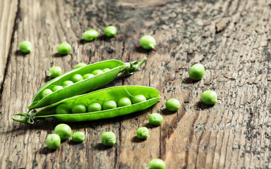 Opened green pea pods with peas in an old wooden table, selectiv