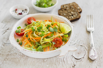 fresh salad with zucchini and carrots in a vintage plate