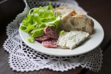 Gorgonzola cheese, sausage and ciabatta on a white plate