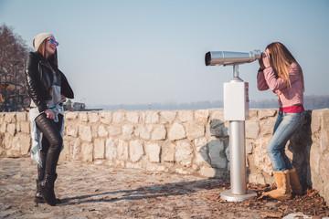 Girl posing in front of binoculars telescope