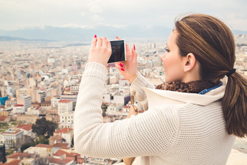 Girl taking picture of a city with her mobile phone