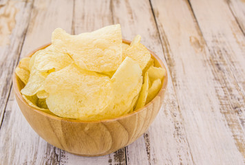 Potato chips in wooden bowl on white wooden table