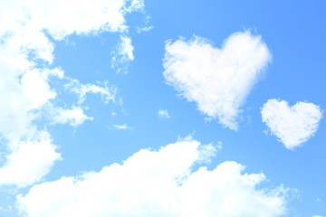 White clouds in shape of hearts on blue sky background