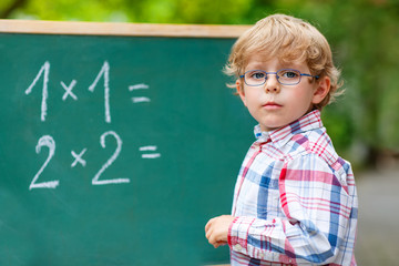 Preschool kid boy with glasses at blackboard practicing mathemat