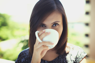 Thai woman drinking hot beverage outside on a sunny day