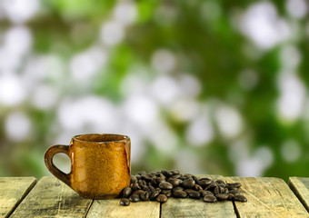 Coffee cup and coffee beans on wooden with green nature backgrou
